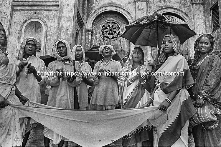 People from Boishnob religous cast asks for alms from public at a ghat by the river Ganga in Kolkata, India