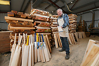 BNPS.co.uk (01202) 558833<br /> Pic: ZacharyCulpin/BNPS<br /> <br /> Tim in the workshop with the cut willow (top half of the picture) that is ready to be shaped into cricket bats<br /> <br /> Master bat maker Tim Keeley is putting the finishing touches to his beautifully hand-crafted pieces of willow ahead of the forthcoming cricket season.<br /> <br /> Tim, 62, has made almost half a million bats since starting out as an apprentice at Gray Nicholls aged 16 in 1975.<br /> <br /> He is the founder of family business Keeley Cricket, in Battle, East Sussex, which he runs with his brother Nick who has 35 years of bat-making experience.