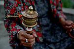 A lady spins a prayer wheel. Bhutan is a Buddhist country.  Arindam Mukherjee..