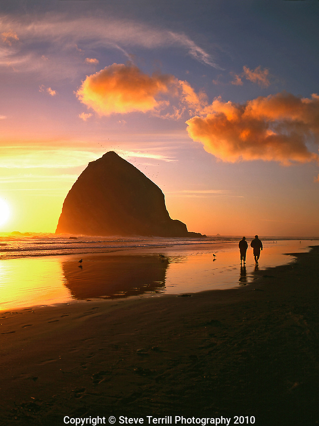 Couple walking beside Haystack Rock at sunset at Cannon Beach, Oregon