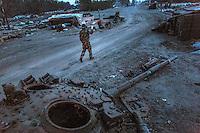 UKRAINE, 03.2015, Stanitsa Luganskaja. In dem Frontdorf passiert ein ukrainischer Soldat einen von Separatisten zerstoerten Kampfpanzer.   In this frontline village a Ukrainian soldier is passing by a battle tank destroyed by separatists.  © Arturas Morozovas/EST&OST