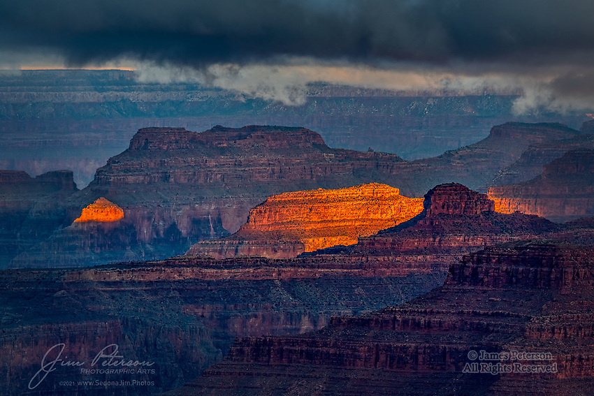 October Sunrise at South Rim.  An early autumn storm was moving out as dawn sunbeams broke through the clouds, casting a warm glow wherever they landed in the myriad depths of the Grand Canyon.<br /> <br /> Image ©2021 James D. Peterson