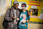Two male students interacting in corridor between classes.