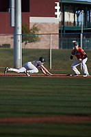 First baseman Garrett James (18) of Fort Bragg High School in Fort Bragg, California waits for a throw as David Wilson (16) of Akins High School in Austin, Texas dives back during the Baseball Factory All-America Pre-Season Tournament, powered by Under Armour, on January 14, 2018 at Sloan Park Complex in Mesa, Arizona.  (Freek Bouw/Four Seam Images)
