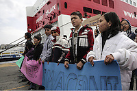 Pictured: Protesters march next to a ship Tuesday 08 March 2016<br />Re: Afghan migrants hold a protest at Piraeus port, near Athens, Greece.