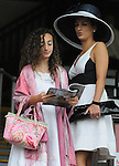 29 August 2009: Lerina Velasquez, 11, and her cousin Tracey Taormina look at past performances for the 8th race at Saratoga Race Track in Saratoga Springs, New York.  Lerina's father John Velasquez later won the race aboard Bulldogger.