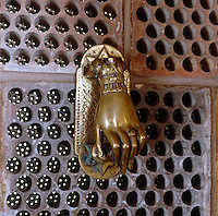 A door knocker in the shape of an Oriental hand is used as an ornament on the bathroom wall