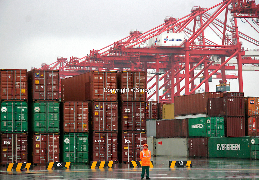 A dock worker standing near the container loading area at the just completed Yangshan Deep Water Port in Shanghai, China. The port will give the city it's first deep water port, adding capacity to its formidable shipping infrastructure,  already Shanghai is expected to become world's largest freight port at the end of this year surpassing Singapore, according to materials provided by the Ministry of Commerce..11 Dec 2005