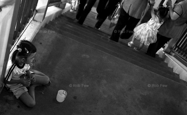 """Two sides of the poverty divide. A child beggar sits alone on an overpass outside one of Bangkok's most expensive shopping centres while a more prosperous girl of the same age passes by with her parents.<br /> <br /> Since 1960, income inequality in Thailand has """"relentlessly gotten worse"""" according to UNDP's 2006 Human Development Report for Thailand.<br /> <br /> The US State Department estimates that there are as many as 20,000 children living and working on the streets of Thailand's major cities (US Human Rights Report for Thailand 2006). <br /> <br /> The majority of these are foreign children who have migrated to Thailand with their families or been trafficked and forced to work as beggars or street vendors.<br /> <br /> As the gulf in income levels widens between Thailand and its neighbours, the problem of street children is set to get worse."""