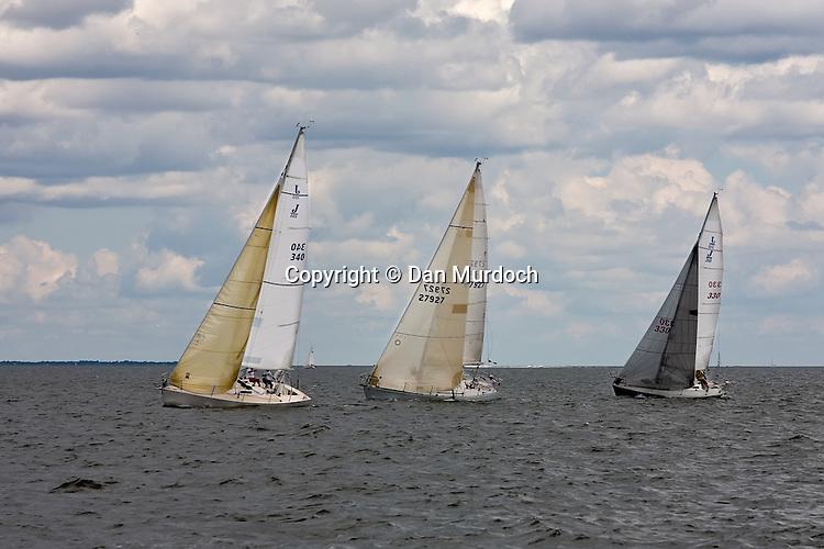 racing sailboats under a cloudy sky