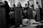 """Amber Blankenship, 5, takes a peek at Wooster, guidedog for Maggee (cq Maggee) Jespersen, second from left, who prayed with others on Ash Wednesday, Feb. 25, 2009, at Cathedral of the Sacred Heart in Raleigh.  Jespersen, who has lost most of her eyesight due to retinitis pigmentosa, says of Wooster, """"My faith is totally turned over to him, and I lean on him every day.  I feel safe and secure when he's leading me.""""  Jespersen was sad because her yellow lab, age 9, is about to retire, and she'll have to find a new dog.  """"He's just getting tired,"""" she said.  Seeing Wooster age, and dealing with an accelerated loss of her eyesight over the past 6 months, are challenges that Jespersen believes have a purpose.  """"Everything is a lesson from God,"""" she said. """"These challenges are helping me get to a better place.""""  Staff photo by Ted Richardson/The News & Observer"""