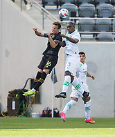 LOS ANGELES, CA - APRIL 17: Danny Musovski #16 of LAFC and Jhohan Romaña #3 Austin FC battle in the air for a ball during a game between Austin FC and Los Angeles FC at Banc of California Stadium on April 17, 2021 in Los Angeles, California.