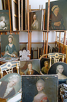 A collection of female portraits is humourously displayed in a storage room
