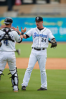 Biloxi Shuckers relief pitcher Nate Griep (24) shakes hands with catcher Max McDowell (4) after closing out a Southern League game against the Montgomery Biscuits on May 8, 2019 at MGM Park in Biloxi, Mississippi.  Biloxi defeated Montgomery 4-2.  (Mike Janes/Four Seam Images)