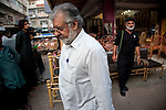 13 April 2013, Karachi, Pakistan:  Muhammad Atiq Mir , Chairman of the Federation of Pakistan Chambers of Commerce and Industry walks with his armed bodyguard to  his premises in the Arambagh Furniture Market in Karachi where he runs a business.  Karachi is a city wracked by violence and many fault lines that span Taliban infiltration, mafia rackets, sectarian violence and corruption from politicians and security forces. Picture by Graham Crouch/The Australian