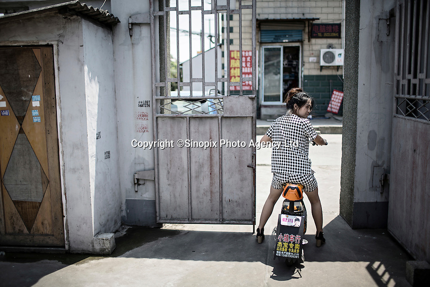 A woman rides her scooter out of a gate in Xingxing village on the outskirts of Shanghai,  China on 14 August 2015.  As China's sputtering economy has beginning to affect employment, many migrants who used to live in the village to work on Shanghai's numerous construction sites and factories are beginning to thin out.