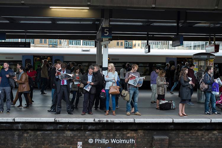 Commuters waiting on a platform at London Bridge station.