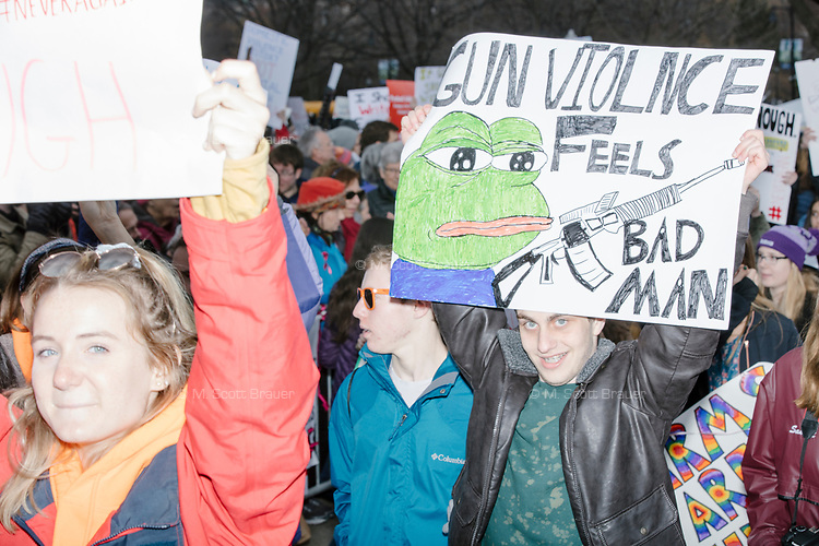"""Students enter Boston Common after marching to the park from Roxby Crossing during the March For Our Lives protest and demonstration in Boston, Massachusetts, USA, on Sat., March 24, 2018. The march was held in response to recent school gun violence. Here, people hold a sign with Pepe the frog reading, """"Gun violence feels bad man."""""""