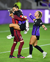 ORLANDO, FL - APRIL 21: Ali Riley #7 of the Orlando Pride leaps into the arms of Ashlyn Harris #24 of the Orlando Pride to celebrate a victory as Courtney Petersen #17 of the Orlando Pride joins after a game between Washington Spirit and Orlando Pride at Exploria Stadium on April 21, 2021 in Orlando, Florida.