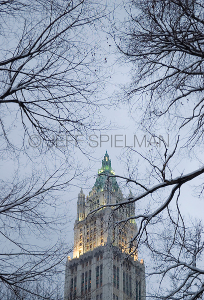 "The Woolworth Building Viewed Thru Snow Covered Trees at Dusk, City Hall Park, Civic Center, Lower Manhattan, New York City, New York State, USA.<br /> <br /> The Woolworth Building at 233 Broadway was completed by the architect Cass Gilbert in 1913.  Built in the Neo-Gothic style with terra cotta detail, it was the tallest building in the world  (792 ft. high) until it was supersceded by The Chrysler Building on 42nd Street in 1930.  The building was the headquarters of the F.W. Woolworth and Co. chain of Five and Dime Stores.  When the building opened it was dubbed ""The Cathedral of Commerce"" by the Brooklyn minister and radio evangelist Rev. S. Parkes Cadman."