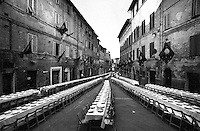 © Francesco Cito / Panos Pictures..Siena, Tuscany, Italy. The Palio. ..Each contrada (city district) holds a banquet on the evening before the race...Twice each summer, the Piazza del Campo in the medieval Tuscan town of Siena is transformed into a dirt racetrack for Il Palio, the most passionately contested horse race in the world. The race, which lasts just 90 seconds, has become intrinsic to the town's heritage since it was first run in 1597...