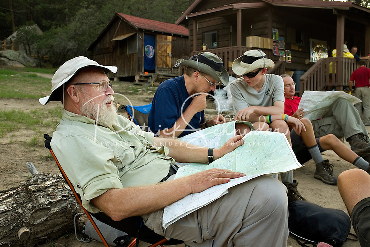 Photo story of Philmont Scout Ranch in Cimarron, New Mexico, taken during a Boy Scout Troop backpack trip in the summer of 2013. Photo is part of a comprehensive picture package which shows in-depth photography of a BSA Ventures crew on a trek.  In this photo adult advisors look over their maps, as the Venture crew worked to make plans for their next days hike in the backcountry at Philmont Scout Ranch.   <br /> <br /> The  Photo by travel photograph: PatrickschneiderPhoto.com