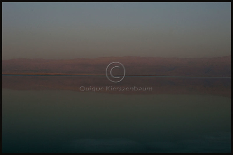 The Jordanian mountains of Moab are reflected at the Dead Sea. The inland sea which separates Israel and Jordan is retreating by about a meter a year as the two countries divert almost 90% of the Jordan River waters that for thousands of years fed the mineral-rich sea. They are now seeking international support for a plan to pipe water north from the Gulf of Aqaba to the Dead Sea to rescue the shrinking sea. Photo by Quique Kierszenbaum