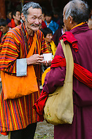 Old friends meet, smile and chat at a traditional Buddhist prayer and social gathering, National Memorial Choeten, Thimpu, Bhutan