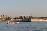 Small ferry boat and cruise ships on the River Nile at Luxor.The town of Luxor occupies the eastern part of a great city of antiquity which the ancient Egytians called Waset and the Greeks named Thebes.