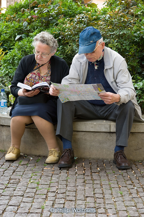 Elderly tourists look at a map and a guide book in central London