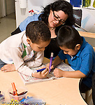 Education preschool 4 year olds female play therapist working with two boys in classroom boys playing a tic tac toe game with markers horizontal
