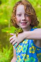 northern green frog, Lithobates clamitans melan, a subspecies of green frog, Lithobates clamitans, girl, holding a frog in front of pond, Catskill Mountains or Catskills, Andes, New York, USA