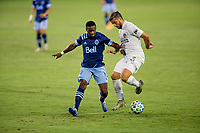 CARSON, CA - OCTOBER 18: Emiliano Insua #3  of the Los Angeles Galaxy moves to the ball past Cristian Dajome #11 of the Vancouver Whitecaps during a game between Vancouver Whitecaps and Los Angeles Galaxy at Dignity Heath Sports Park on October 18, 2020 in Carson, California.