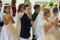Catholic boys and girls receiving the sacrament of first holy communion.