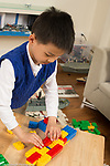 6 year old boy working on ship made of colored plastic building bricks (Duplo)