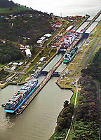 aerial photograph of three vessels passing through the Gatun Locks, Panama Canal, Panama; two vessels are in the locks and one containership waits to enter the locks as a tug boat helps position the ship