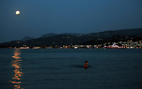 A full moon with a partial eclipse, rises while a young boy cools off in the sea in Oropos in the Evia Bay, 30 miles east of Athens, Greece. Monday 07 August 2017