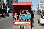 Palestinian children ride in the back of a tuktuk with their father on their way to a street market in Gaza City on December 6, 2019. Photo by Osama Baba