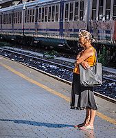 Urban Street Photography at the Termini station in Rome Italy.  The Termini station with it's graffiti covered trains is the background for this photograph. <br />