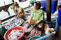 Thailand. Bangkok. The family / mother and daughter) lives in Tha Tian and has built along the river bank and above the Chao Phraya River an illegal squatter house. The family makes a living by producing dried fishes products for sale. Tha Tian is a community located in the downtown area and in the center of the urban historic district, called Koh Rattanakosin. 30.03.09 © 2009 Didier Ruef