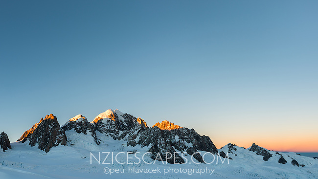 Sunrise over second highest peak of Southern Alps, Mount Tasman 3497m in centre with Mt. Lendenfeld 3194m and Mount Haast 3114m on left and Torres Peak 3160m on right, Tasman Sea far right on horizon, Westland Tai Poutini National Park, West Coast, UNESCO World Heritage, New Zealand, NZ