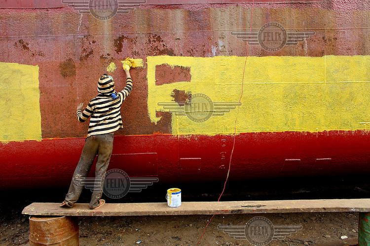 A labourer works on the construction of a ship at a ship building yard in Dhaka. He paints the side of the ship.  Workers get around 300 Tk (about GBP 2.45) per day for working at the yard.