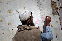 A Pakistani health officer writes information about vaccination for poliomyelitis at a house's wall, during door-to-door 'Anti-polio campaign' in Karachi, Pakistan on Jan. 19, 2015