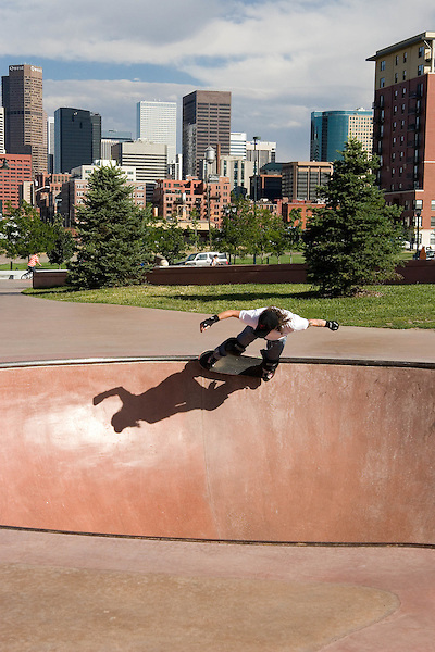 Young person skateboarding at the Denver Skatepark, downtown Denver skyline behind, Denver, Colorado, USA .  John offers private photo tours in Denver, Boulder and throughout Colorado. Year-round.