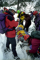Mountain search and rescue team having found a walker that was seriously injured on a mountainside in snowy conditions.  The casualty has been  covered by a ripstop waterproof nylon cover to protect him from the weather. The team paramedic is assessing the casualty for injuries prior to evacuation...© SHOUT. THIS PICTURE MUST ONLY BE USED TO ILLUSTRATE THE EMERGENCY SERVICES IN A POSITIVE MANNER. CONTACT JOHN CALLAN. Exact date unknown.john@shoutpictures.com.www.shoutpictures.com...