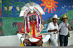 A Naua Indian dancer stands next to a mural in the school of the village of Ayotzinapan, Puebla. Photo by Heriberto Rodriguez/ CGEIB