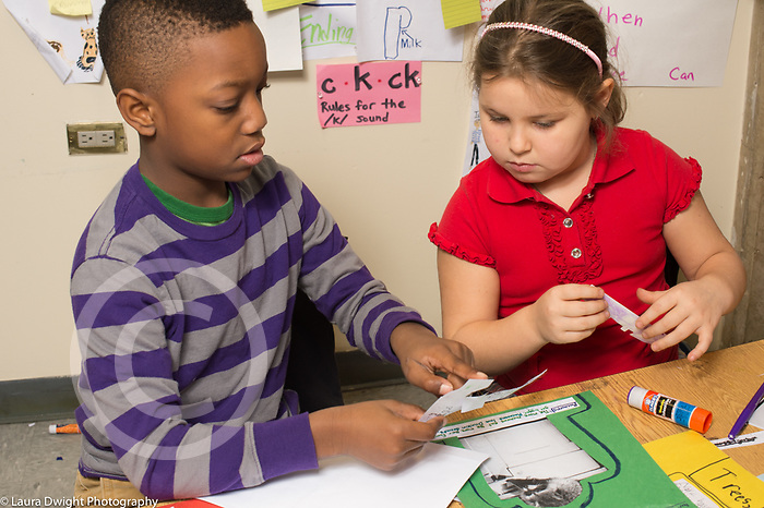 Education elementary school second grade boy and girl working together on project