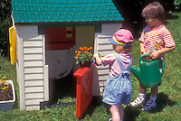 Little boy and girl gardening, watering flowers marigolds in kids playhouse, in backyard on sunny summer day. Redheaded child, Caucasian children