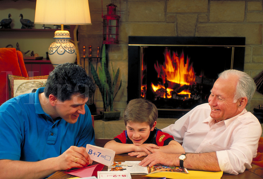 Boy and father have fun playing a tablegame in the living room with grandfather. Three generations of Caucasian family. Grandfather, father and child.