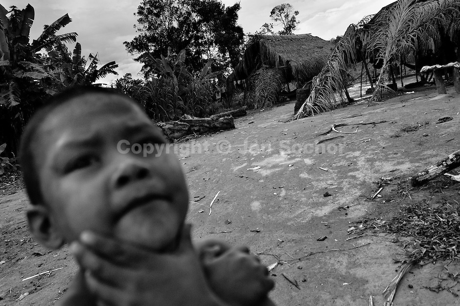 A displaced Indian boy (Nukak Maku) stands in front of the shacks in a refugee settlement close to San Jose del Guaviare, Meta dept., Colombia, 4 September 2009. With nearly fifty years of armed conflict, Colombia has the highest number of civil war refugees in the world. During the last ten years of the civil war more than 3 million people have been forced to abandon their lands and to leave their homes due to the violence. Internally displaced people (IDPs) come from remote rural areas, where most of the clashes between leftist guerrillas FARC-ELN, right-wing paramilitary groups and government forces takes place. Displaced persons flee in a hurry, carrying just personal belongings, and thus they inevitably end up in large slums of the big cities, with no hope for the future.